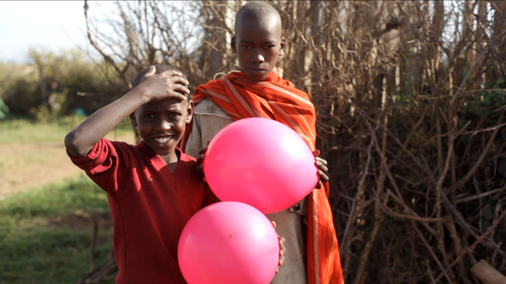 Kids holding baloons next to Sadhana Forest Kenya