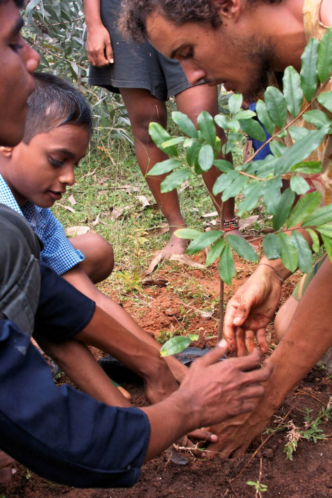 Tiago and children planting a tree